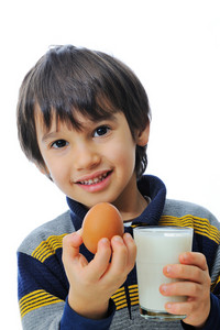 Cute little kid with glass of milk and egg