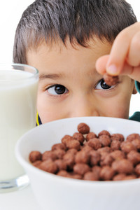Portrait of a nice boy with cereals and milk