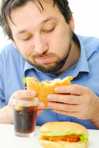 Handsome man enjoying burger and coke