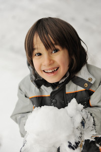 Cute little kid holding snowball