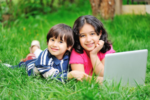 Children in nature with laptop