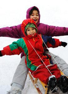 Boy and girl sledging on snow