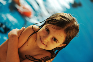 Little cute  girl  in blue water of the swimming pool