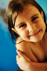 Little cute girl in pool smiling