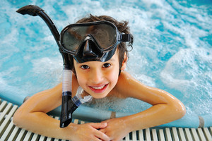 Kid in pool with diving equipment
