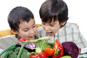 Two little boys eating vegetables