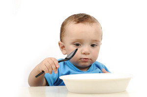 Cute adorable one year old baby with green eyes eating on table