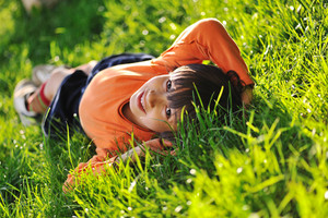 Happy boy laying on beautiful morning green grass