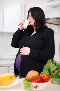 Pregnant woman drinking milk in kitchen