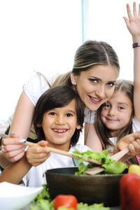 Beautiful mother with  little son and daugther in kitchen together
