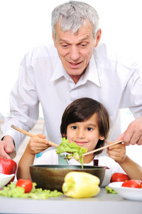 Grandfather and little boy in kitchen cooking together