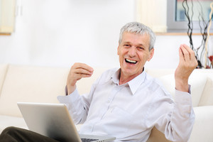 Senior good looking man with laptop at home