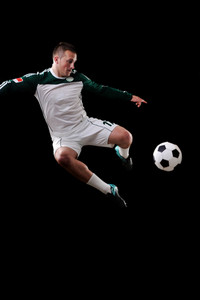 Soccer player in the air over black background