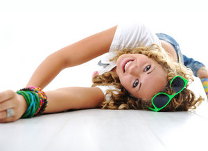 Teen cute girl with curly hair lying on floor