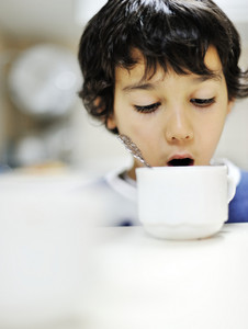 Kid in kitchen drinkin from the cup