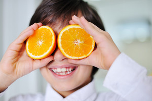 Little boy holding orange slices on eyes as sunglasses