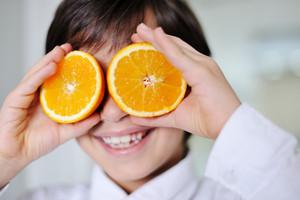 Little kid  hplaying with fresh orange fruits