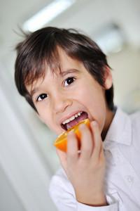 Child eating fresh orange fruit