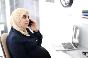 Pregnant Muslim Arabic business woman talking on phone