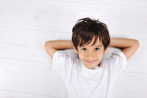 Little boy laying relaxed on white floor at home