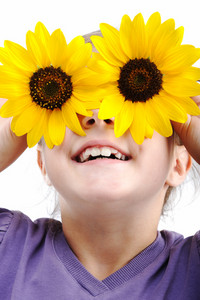Happy little girl with sunflowers on eyes