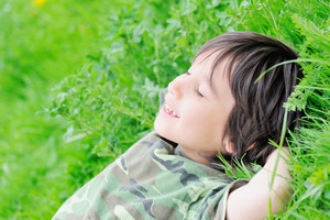 Cute little boy laying on grass