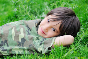 Cute little kid laying on grass
