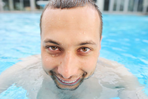 Closeup portrait of a handsome funny and happy young man in pool