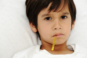 Sick little boy with thermometer