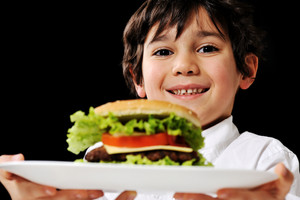 Little boy offering a hamburger on plate