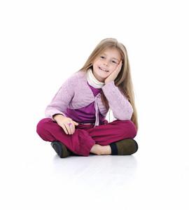 Portrait of a cute little girl sitting on floor