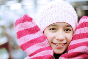 Portrait of a beautiful smiling girl wearing winter hat and gloves