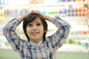 Kid with hands on his head in shopping mall