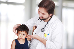 Young doctor examining little boy in hospital