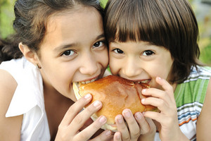 Closeup of two children eating sandwich in nature together