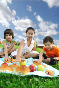 Small group of children eating together in nature