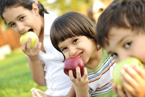 Small group of children eating apples together