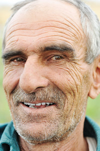 Face portrait of a wrinkled cheerful smiling senior man