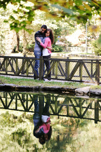 Young couple loving each other on river in nature with reflection in water