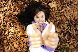 Young beauty girl laying on autumn ground and leaves with thumbs up