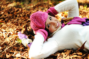 Young beauty girl laying on autumn ground and leaves