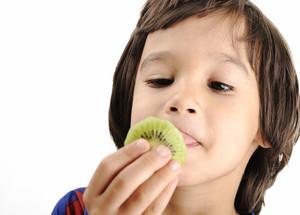 Young boy eating kiwi