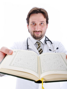 Muslim doctor with Koran in hands showing you open pages