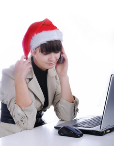 Beautiful business woman is working in office in santa claus hat - talking on cell phone