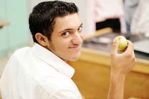 Student in collage with an apple in hand smiling