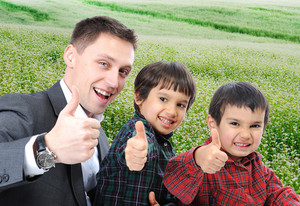 Young father and two sons outdoor sitting and rising thumb up