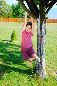 Little cute girl is playing on tree