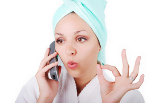 Beautiful sexy girl with towel on her head speaking on phone