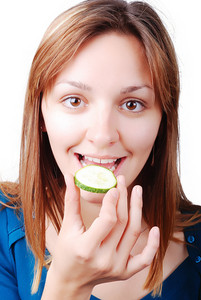 Nice girl about to eat a cucumber