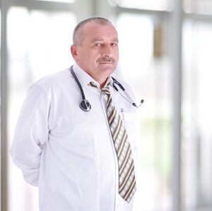 Gray hair expertise handsome senior doctor hospital portrait white corridor